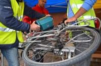 Photo de deux personnes qui gravent le cadre d'un vélo